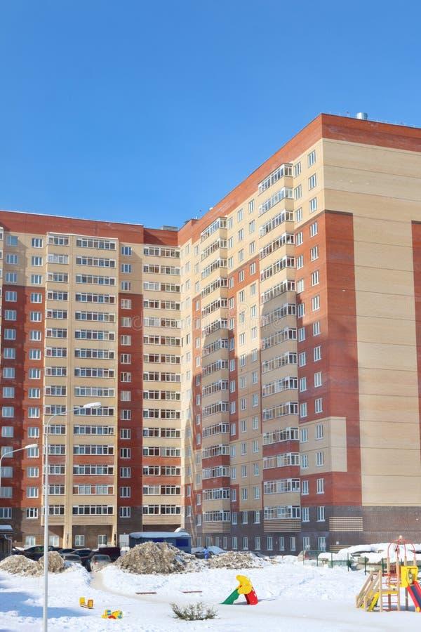 Lekplats och del av bostads- byggnad arkivfoto