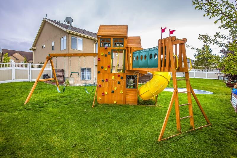 Lekplatsstrukturen med glidbanan svänger lekstugatornet och klättraväggen royaltyfri bild