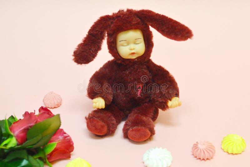 Leksak för flickan på rosa bakgrund arkivbild