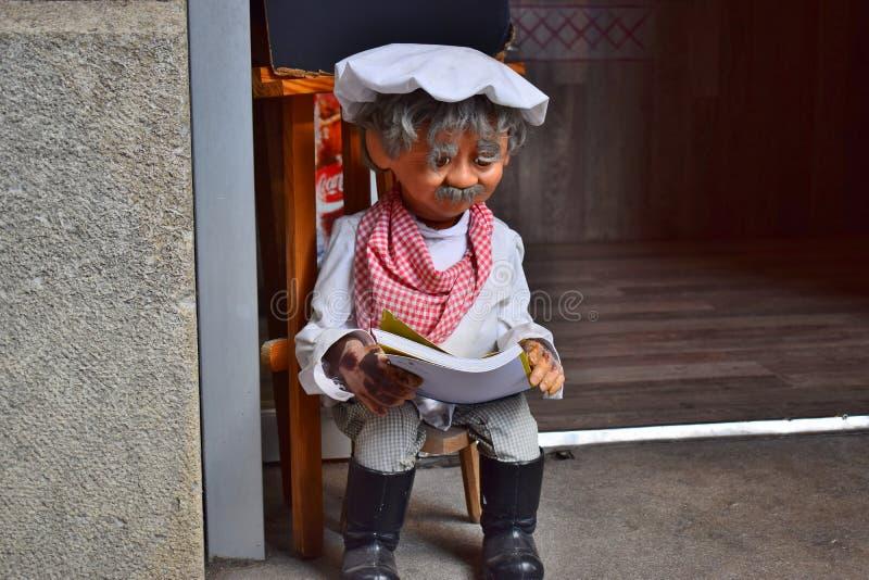 Leksak och att visa en gammal kock som sitter på ingången av restaurangen royaltyfria bilder