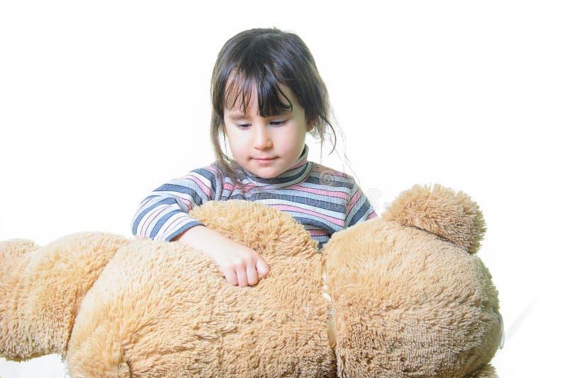 Leksak- och folkbegrepp - gullig liten flicka som kramar nallebjörnen arkivbilder