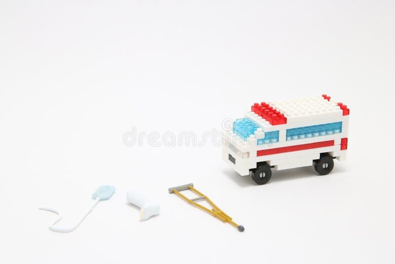 Leksakambulansbil, miniatyrdroppe, gibbs och krycka på vit bakgrund arkivfoto