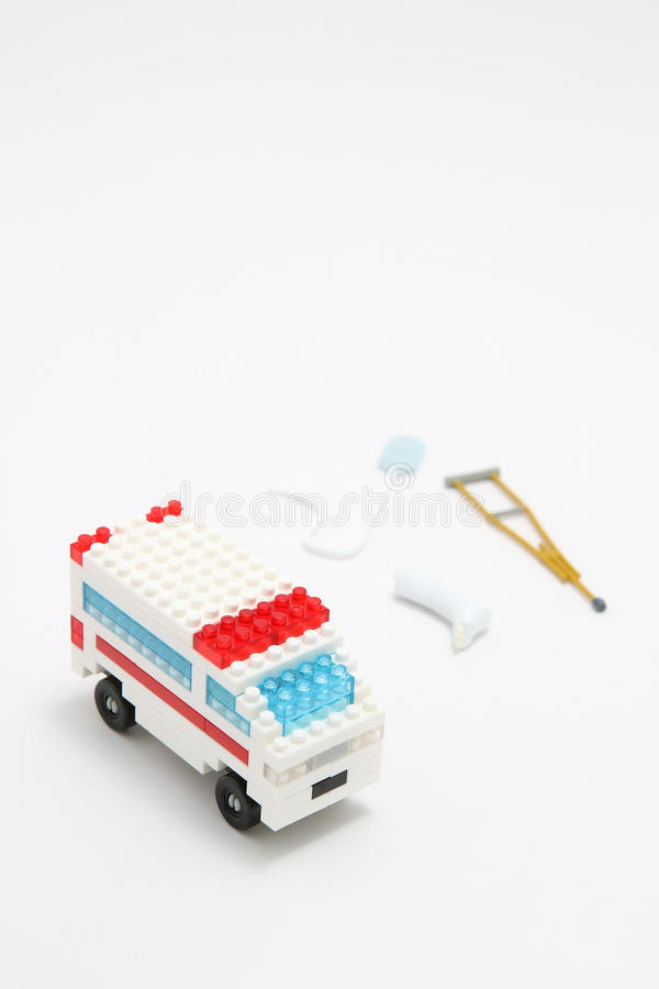 Leksakambulansbil, miniatyrdroppe, gibbs och krycka på vit bakgrund royaltyfri fotografi