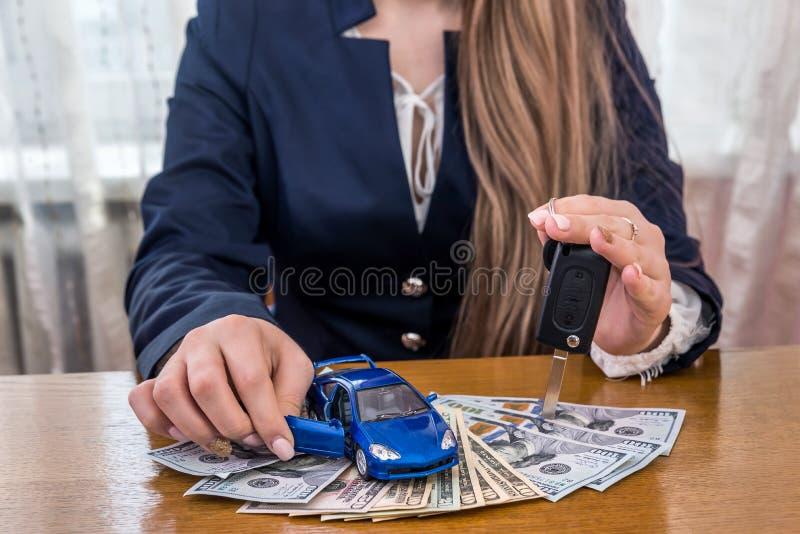 Leksakbil och tangenter i kvinnliga händer på dollar royaltyfri foto