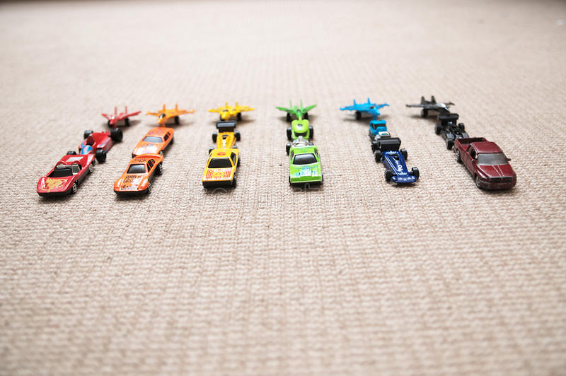 Leksakbilsamling på matta Sorterat av färg Trans.-, flygplan-, nivå- och helikopterleksaker för barn, miniatyr modellerar royaltyfria foton
