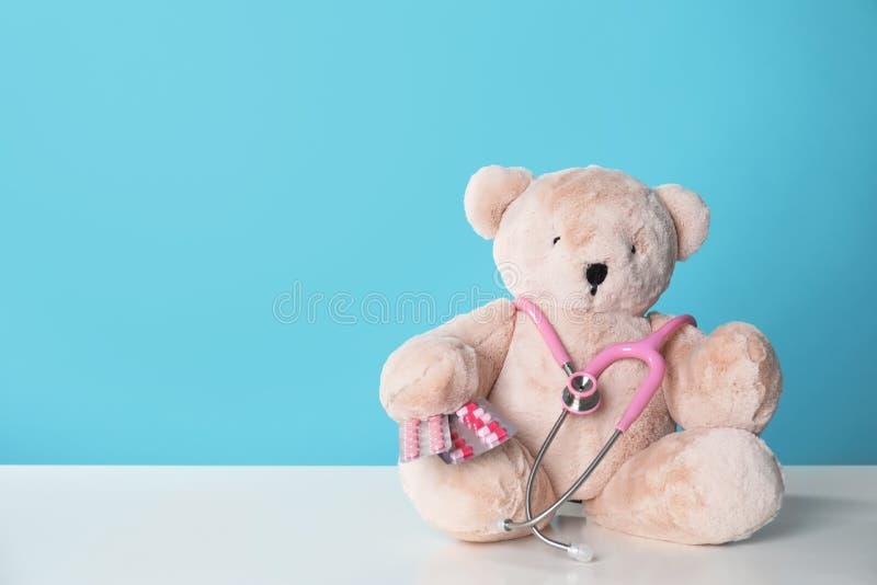 Leksakbjörn med stetoskopet och piller på tabellen mot färgbakgrund Sjukhus för barn` s arkivfoton
