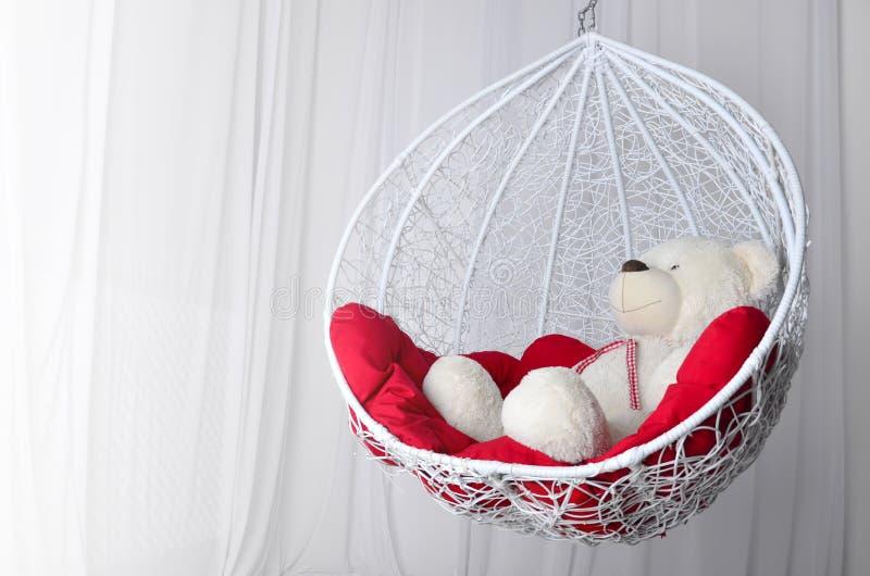 Leksakbjörn och dekorativ gunga med röda kuddar Hemtrevligt ställe som ska kopplas av arkivbilder