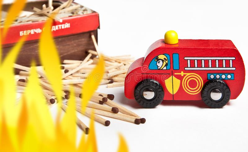 Leksakbrandlastbil bredvid spridda matcher på vit bakgrund arkivfoton
