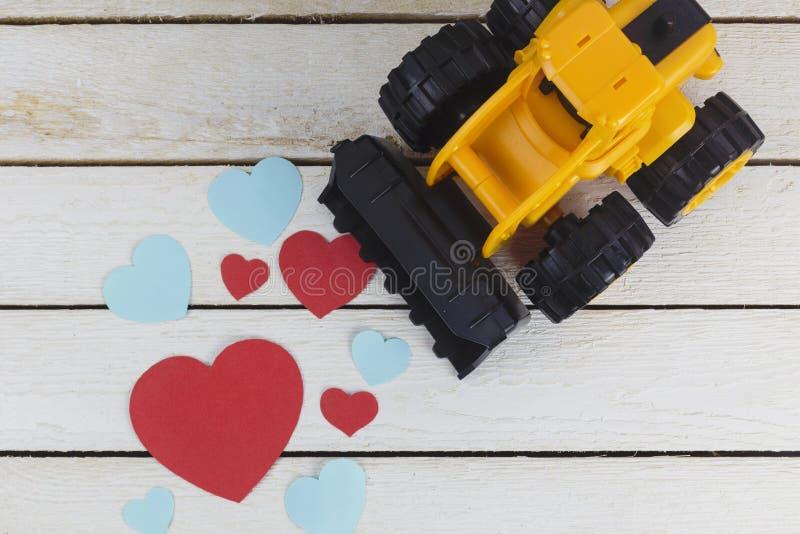 Leksakbulldozern samlar pappers- hjärtor royaltyfria bilder