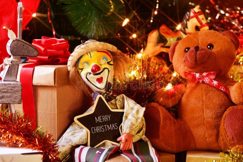 Leksaker och gåvor under ett julträd och en glad jul för text royaltyfri bild