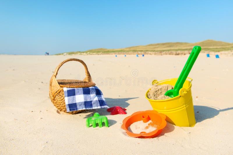 Leksaker och picknickkorg på stranden royaltyfria bilder