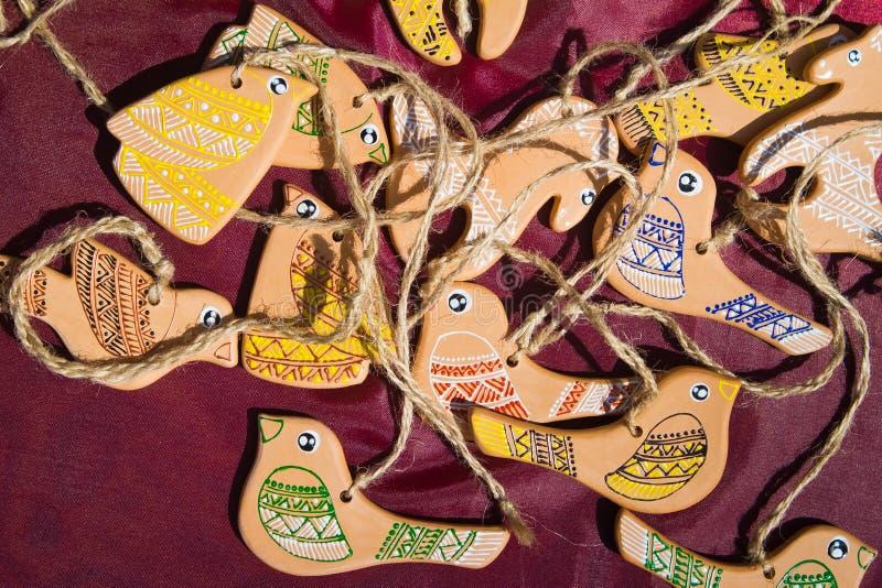 Leksakfåglar och hästar som är handgjorda av lera och som är handpainted med trådar som ska hängas arkivbilder