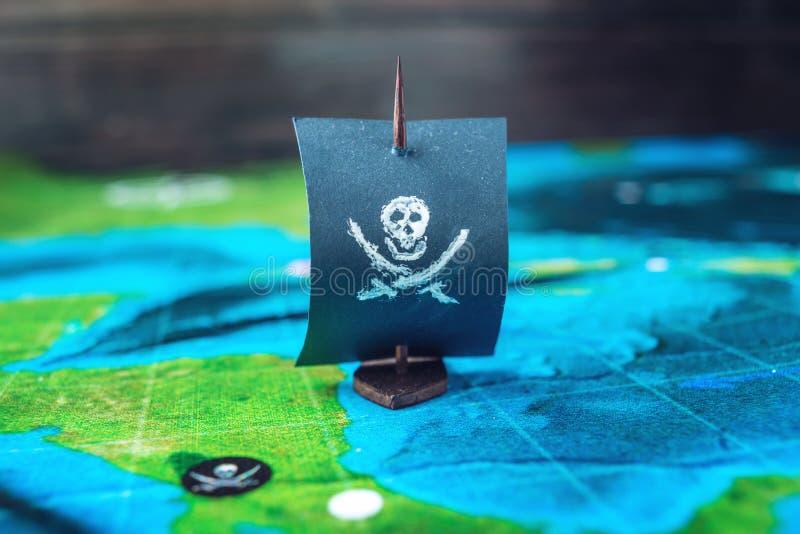 Leksakfartyget piratkopierar flaggaskallen och ben på världskartan av de handgjorda brädelekarna för spelplanen royaltyfri bild