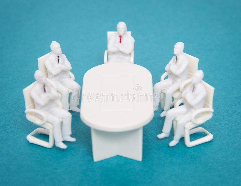 Leksakfolket med band sitter på den samma tabellen Ett begrepp av möte av chefer och av affärsfolk i kontoret, planläggning royaltyfria foton