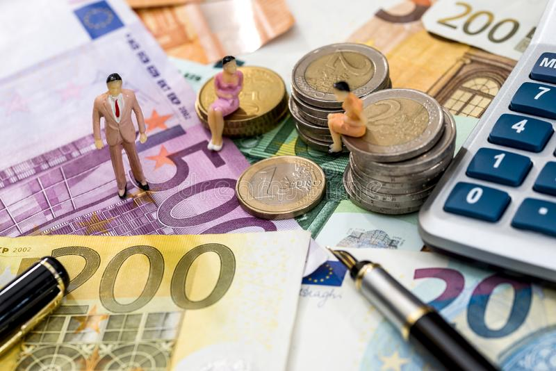 Leksakfolket sitter på euromynt med räknemaskin-, penn- och euroräkningar arkivbild