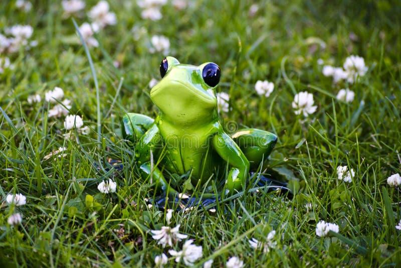 Leksakgroda som sitter i gräset fotografering för bildbyråer