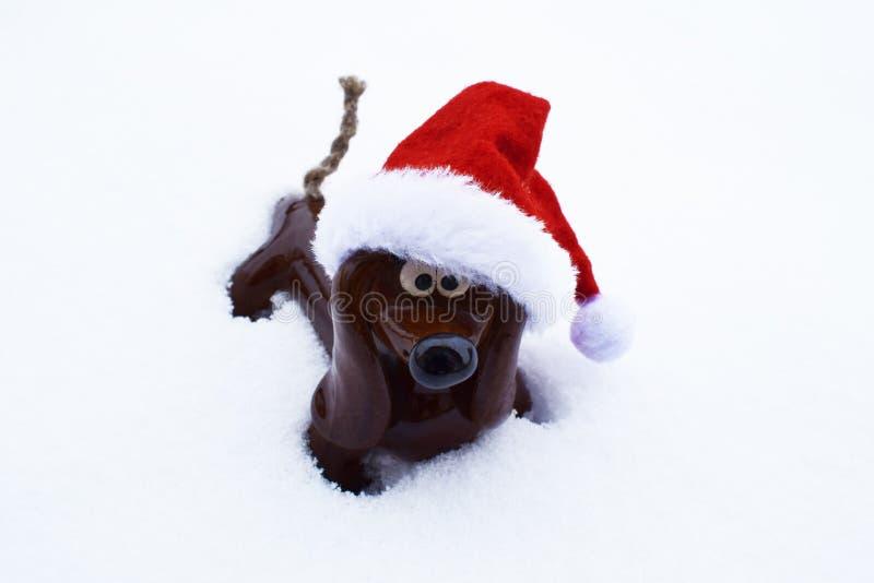 Leksakhund med hatten i snö arkivfoton