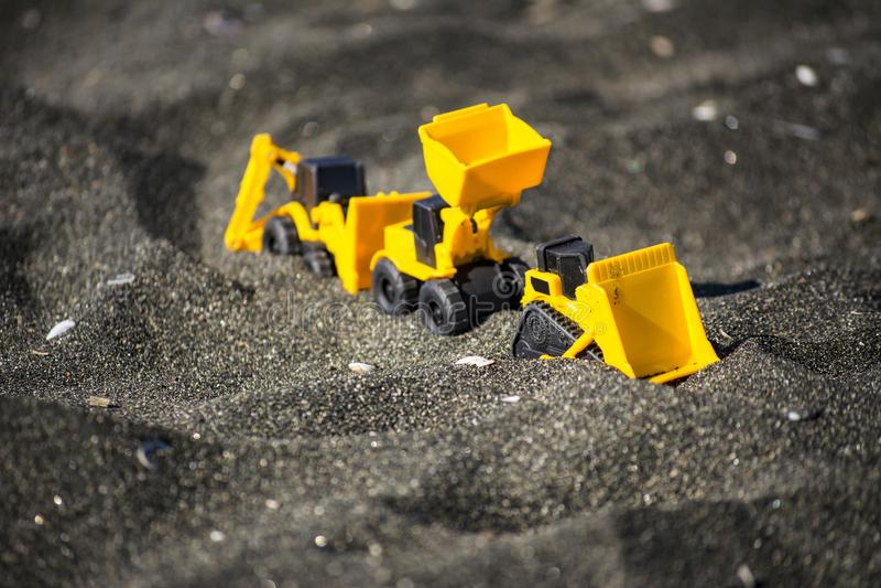 Leksakkonstruktionsmaskineri i svart sand arkivfoto