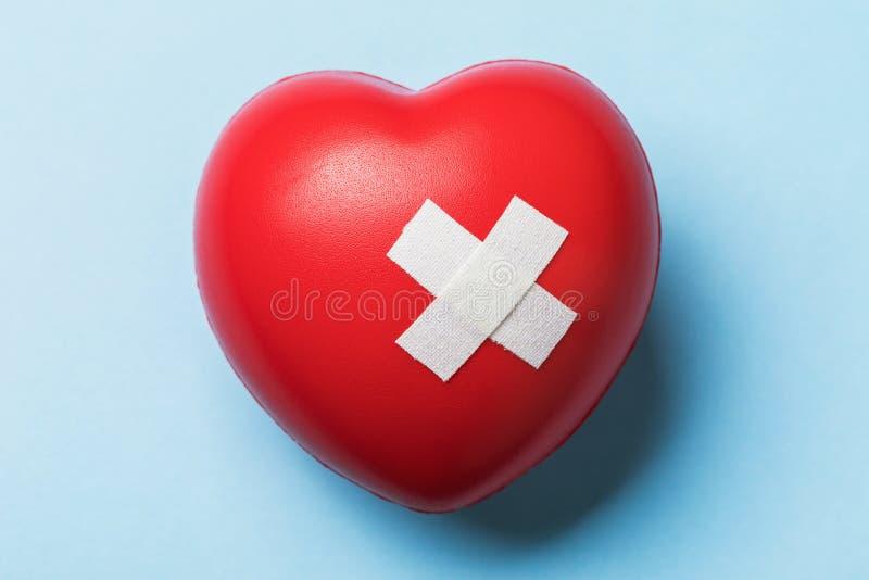 Leksakshjärta förseglat med medicinskt plåster fotografering för bildbyråer