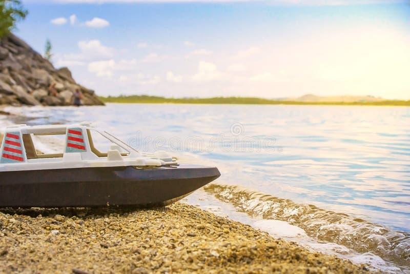 Leksakskepp på den sandiga havkustnärbilden på suddig bakgrund med bokeheffekt arkivbilder