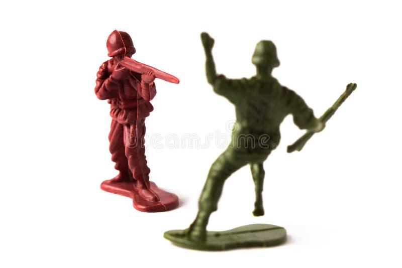 Leksaksoldat som skjuter en fiende som isoleras på vit bakgrund arkivbild