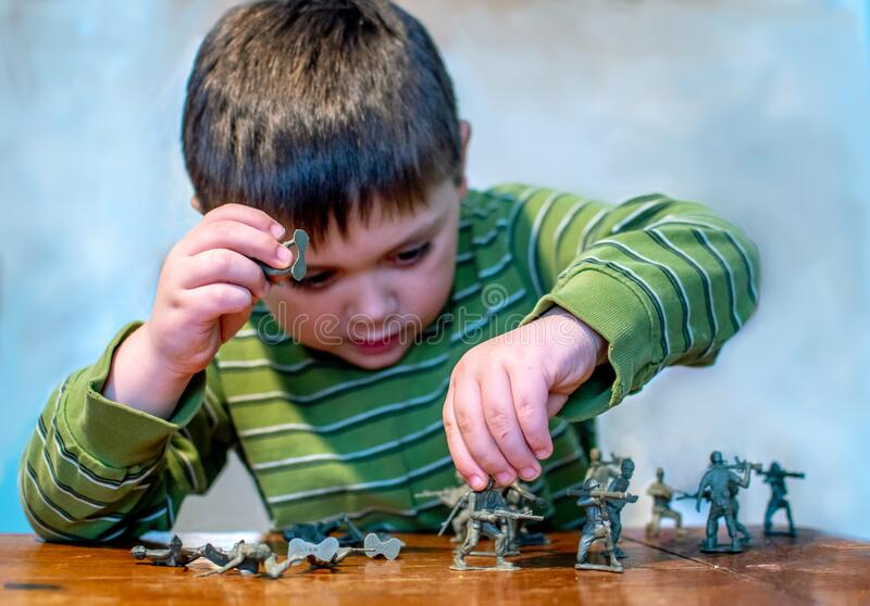 Leksakssoldater på ett bord med en lekfull liten pojke royaltyfria foton