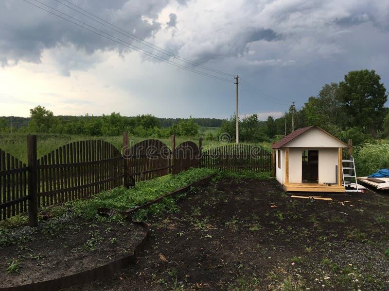 Lekstuga i bygden, staketet och polerna med elektricitetskablar arkivbild