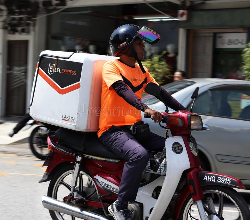 LEL Express Dispatch Rider Out On Delivery In Malaysia. LEL Express or Lazada eLogistics Express courier dispatch rider riding on his container motorcycle out on stock photo