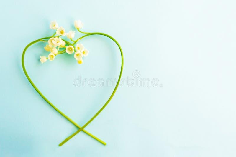 Lelietje-van-dalen in de vorm van een hart op een blauwe achtergrond stock foto's