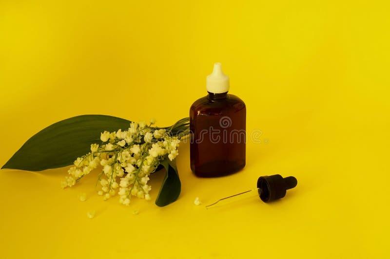 Lelietje-van-dalen, majalis van etherische olieconvallaria met verse bloemen Convallaria op een gele achtergrond stock afbeeldingen