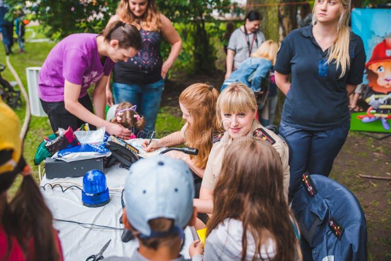 LEMBERG, UKRAINE - Juli 17,2018: Familien mit den Kindern, die durch Park gehen Berufskindertag stockbilder
