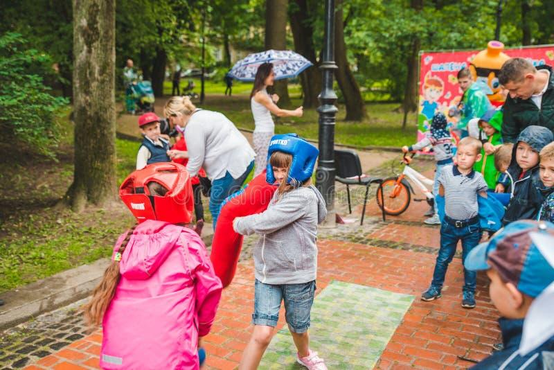 LEMBERG, UKRAINE - Juli 17,2018: Familien mit den Kindern, die durch Park gehen Berufskindertag lizenzfreies stockbild