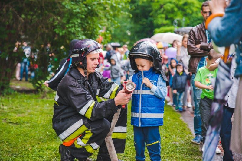 LEMBERG, UKRAINE - Juli 17,2018: Familien mit den Kindern, die durch Park gehen Berufskindertag lizenzfreie stockfotografie