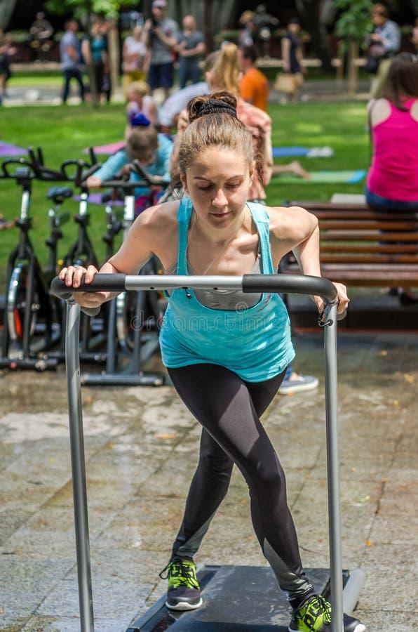 LEMBERG, UKRAINE - JUNI 2016: Junges reizend Sportmädchen in der Straße zeigt verschiedene Übungen auf Eignung lizenzfreie stockfotografie
