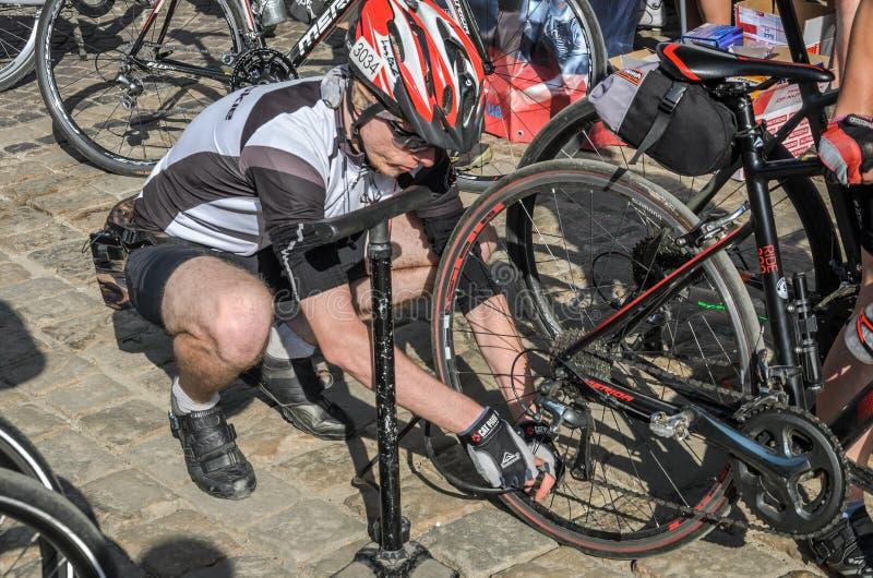 LEMBERG, UKRAINE - MAI 2018: Der Radfahrer repariert sein Fahrrad, indem er ein durchbohrtes Rad pumpt lizenzfreie stockbilder