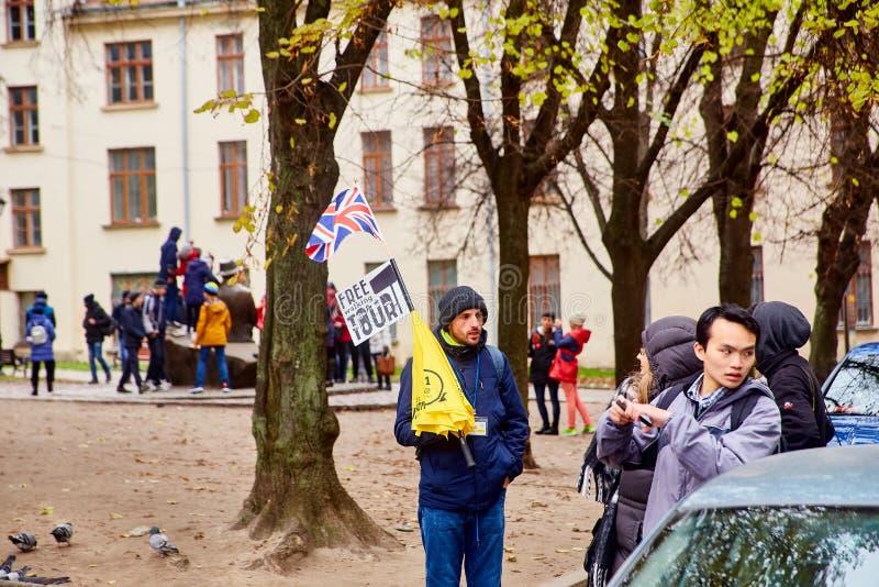 Lemberg, Ukraine - November 2017 Führer nach Lemberg ruft Touristen für eine Exkursion an Ein Mann mit einer britischen Flagge bi lizenzfreie stockbilder