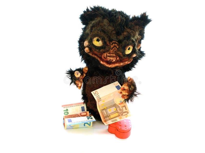 Lembrança da boneca do monstro com contas e coração de dinheiro do Euro fotos de stock royalty free