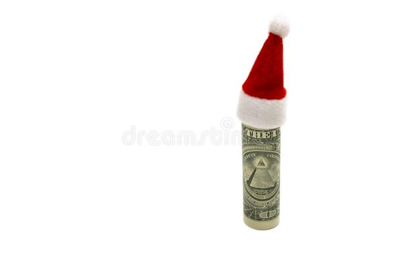 A lembrança que do claus de Santa o chapéu vermelho é vestido em um dólar rolou acima O conceito de custos financeiros para o fer fotos de stock royalty free