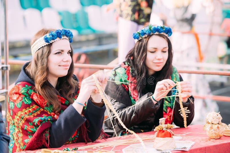 Lembranças criadoras ocupadas das jovens mulheres bonitas da palha em Cele foto de stock