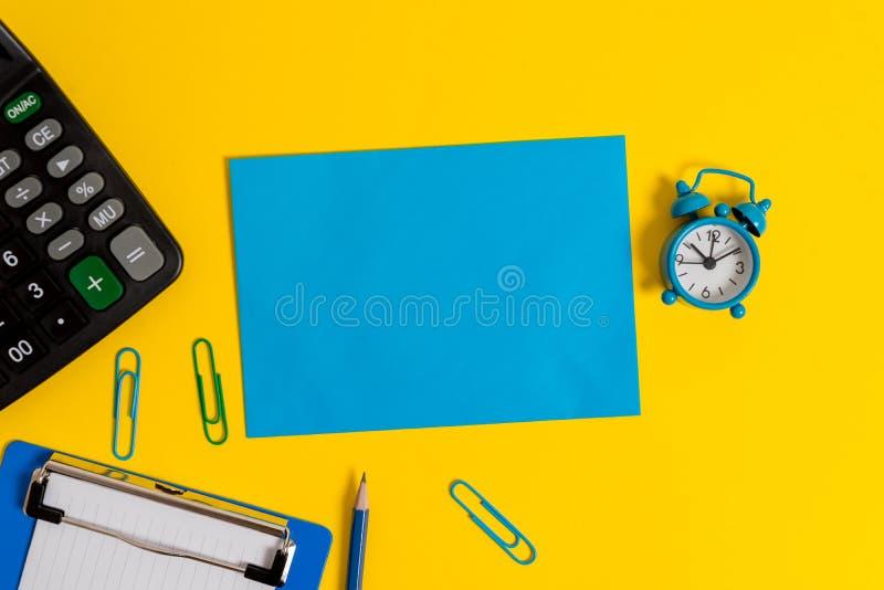 Lembrete colorido de papel vazio da mensagem do fundo da calculadora dos grampos do lápis da nota da folha da prancheta despertad imagens de stock royalty free