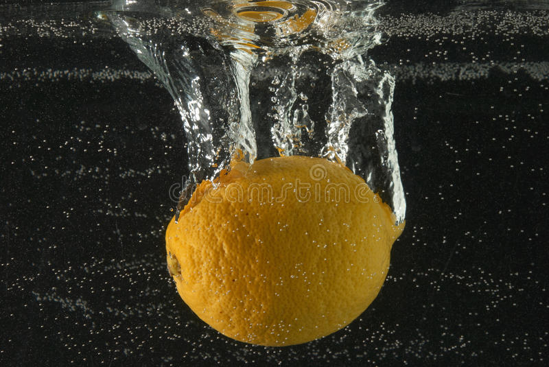Lemon with bubbles. A lemon submerges in water with bubbles royalty free stock photos