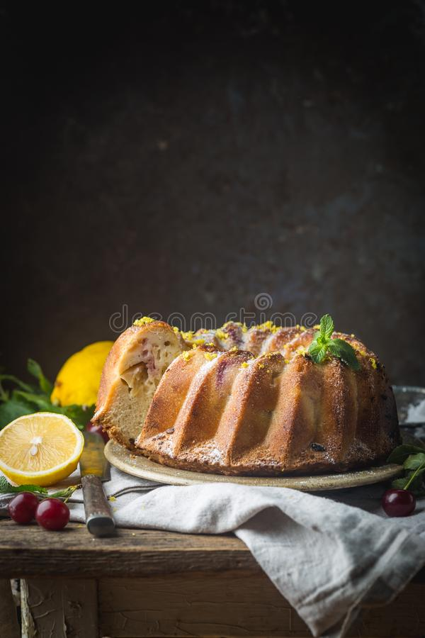 Lemon bundt cake. Homemade lemon bundt cake with icing sugar on a black background stock image