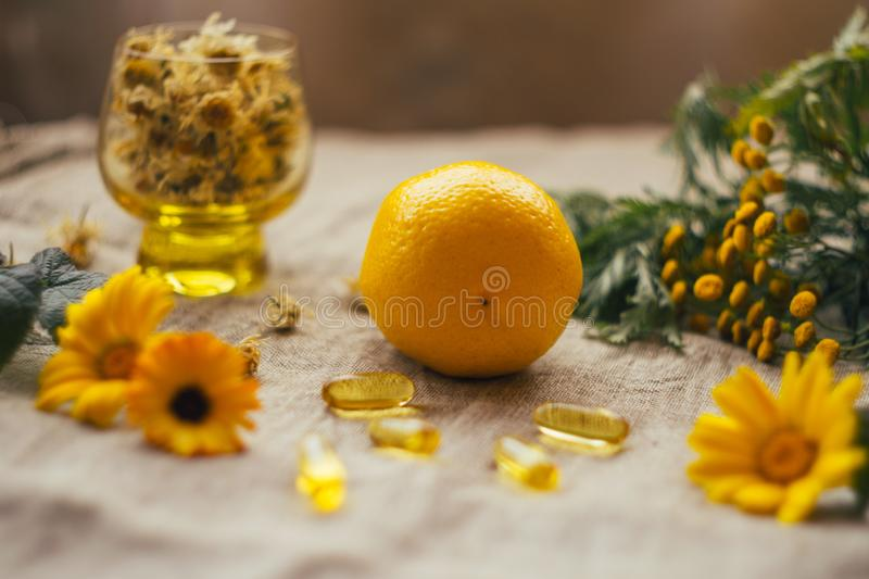 Lemon at burlap sack with omega 3 capsules, tansy, dry chamomile flowers in glass cup, calendula at the table stock images