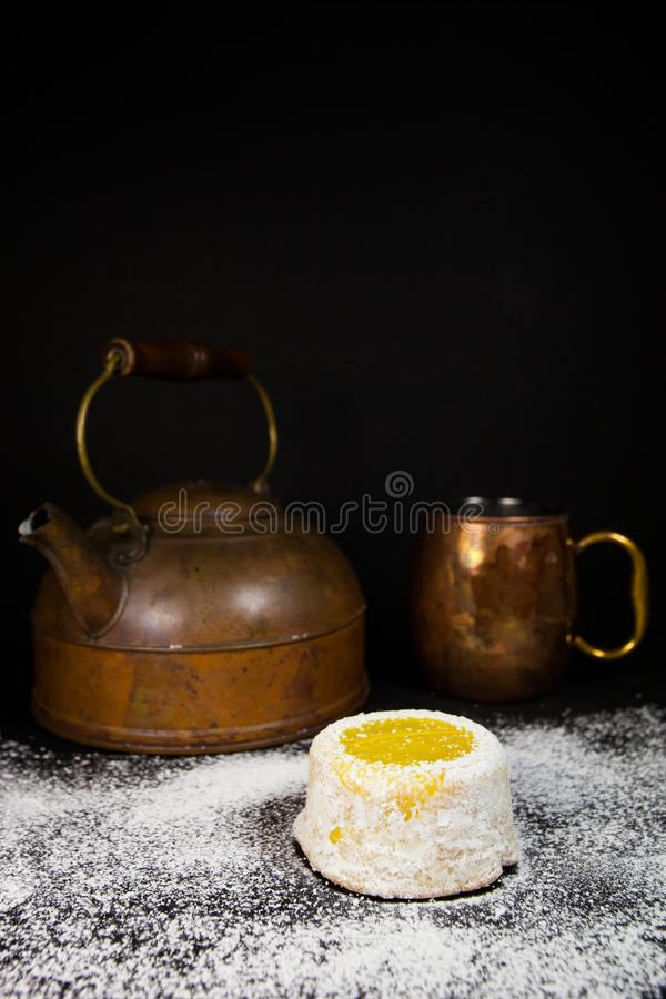 Lemon cake with powdered sugar on dark background with copper tea pot and mug royalty free stock images