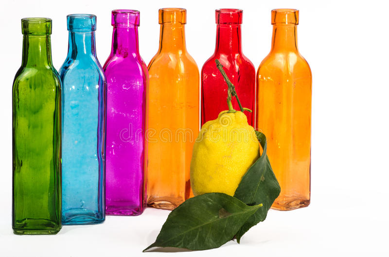 Lemon color. A lemon with six colored bottles on a white background stock photos