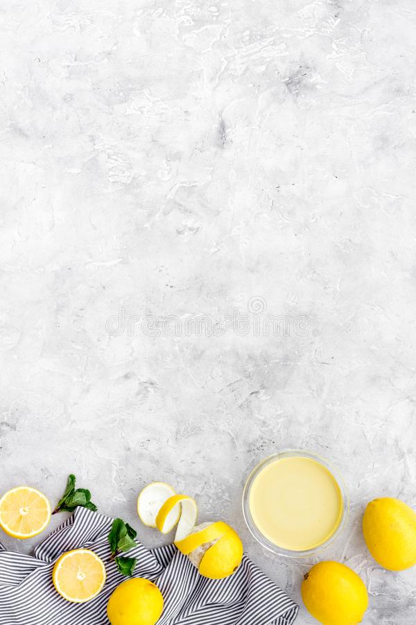 Lemon curd in bowl among lemons on grey background top view copy space stock photo