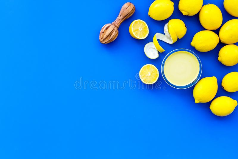 Lemon curd. Sweet cream for desserts near lemons and juicer on blue background top view copy space royalty free stock photography
