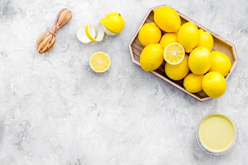Lemon curd. Sweet cream for desserts near lemons and juicer on grey background top view copy space stock image