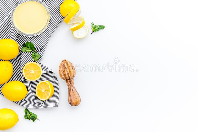 Lemon curd. Sweet cream for desserts near lemons and juicer on white background top view copy space royalty free stock images