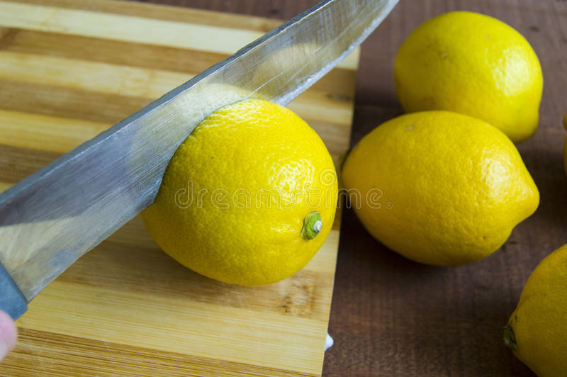 When the lemon is cut,Fresh juicy lemon on top of the salad and fresh for the fish,. Knife and lemon pictures ready to cut on the table,Fresh juicy lemon on top royalty free stock images